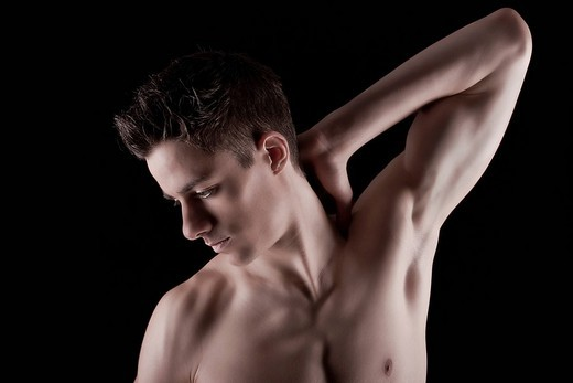 Young muscular man, torso, arms stretched, side view, partial nude : Stock Photo
