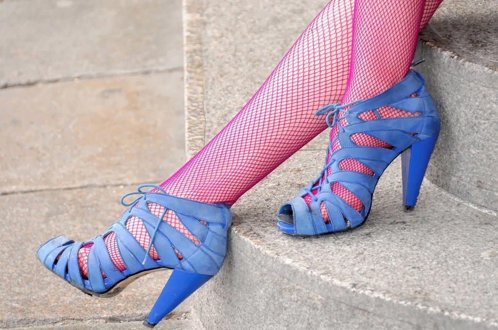 Lady´s legs wearing fashionable blue shoes and pink fishnet stockings, London, England, United Kingdom, Europe : Stock Photo