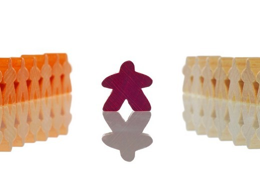 Game marker figure standing between two rows of other game marker figures : Stock Photo