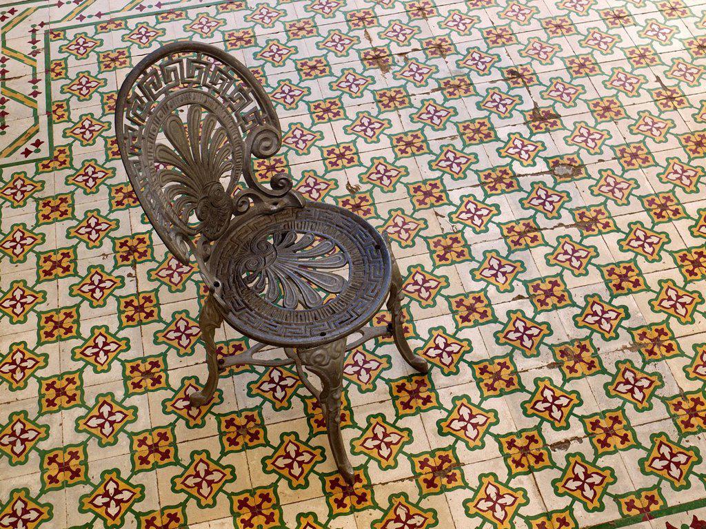 Antique iron chair standing on mosaic tile floor, Trinidad, Cuba, Latin America : Stock Photo