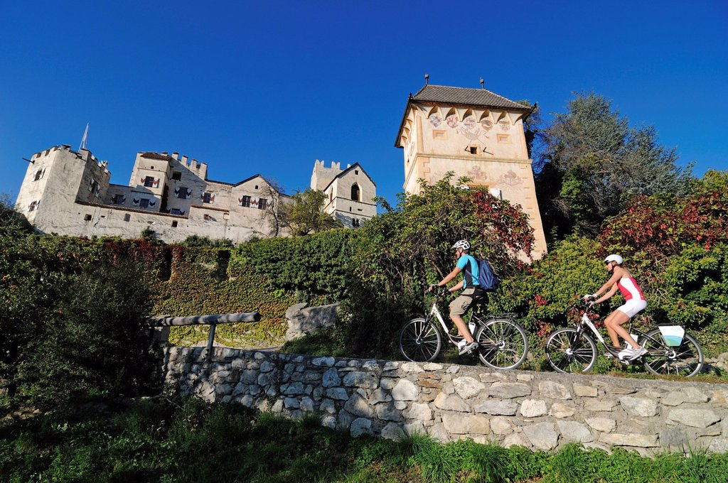 Stock Photo: 1848-646679 Couple riding electric bicycles past Kastelbell castle, Tschars, province of Bolzano_Bozen, Italy, Europe