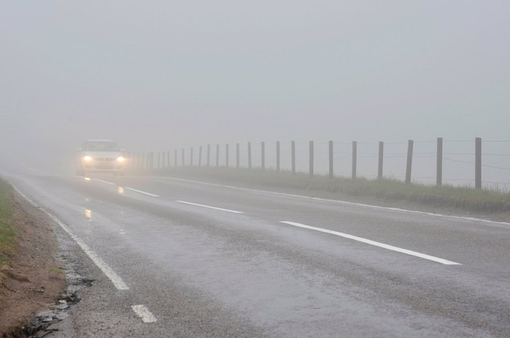 Stock Photo: 1848-647050 Car travelling with headlights on in dense fog on a road in the Scottish Highlands, Grampian Mountains, Scotland, United Kingdom, Europe