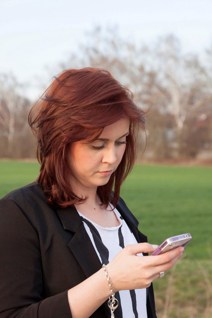 Stock Photo: 1848-647671 Young woman, 25, writing a text message on an iPhone, Germany, Europe