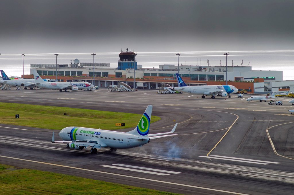 Stock Photo: 1848-648347 Landing approach of passenger plane of Transavia Airlines at the airport of Madeira during bad weather, LPMA, Funchal Airport or Airport Santa Catarina, Madeira, Portugal, Europe, PublicGround