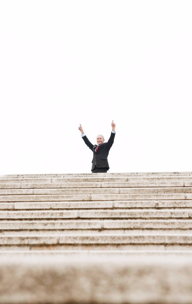 Businessman standing at the top of a staircase, cheering : Stock Photo