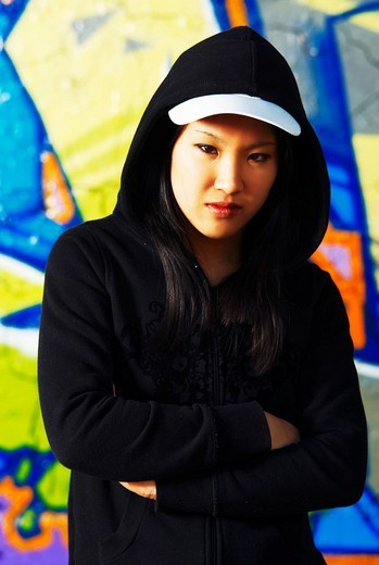 Young Asian girl in rapper pose in front of a graffiti wall : Stock Photo