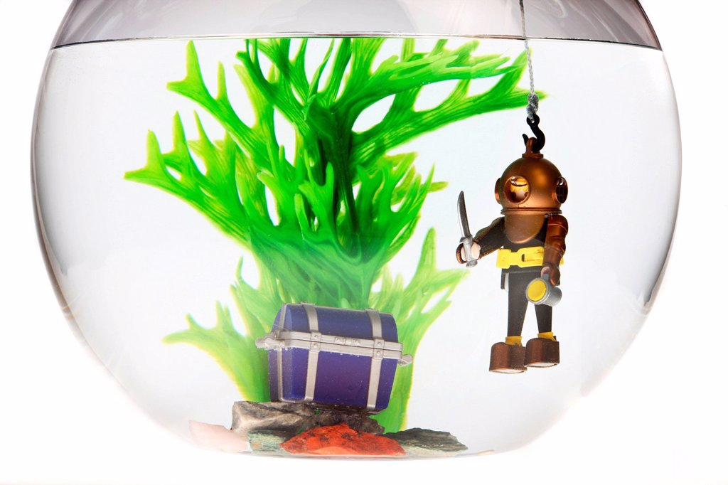 Toy deep sea diver with a treasure chest in a fish bowl, illustration : Stock Photo