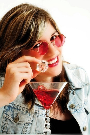 Young woman wearing pink sunglasses and drinking a red drink with an ice cube in her hand : Stock Photo
