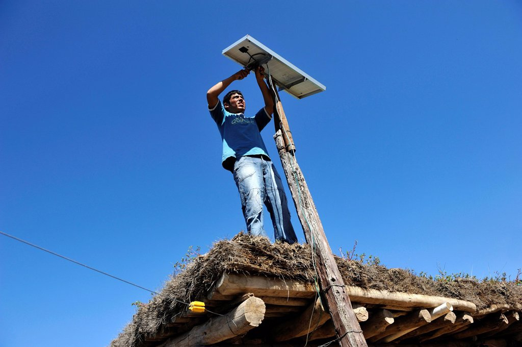 Stock Photo: 1848-650592 Young man mountain solar cells on the roof of a simple hut of a smallholder´s farm, Gran Chaco, Santiago del Estero Province, Argentina, South America