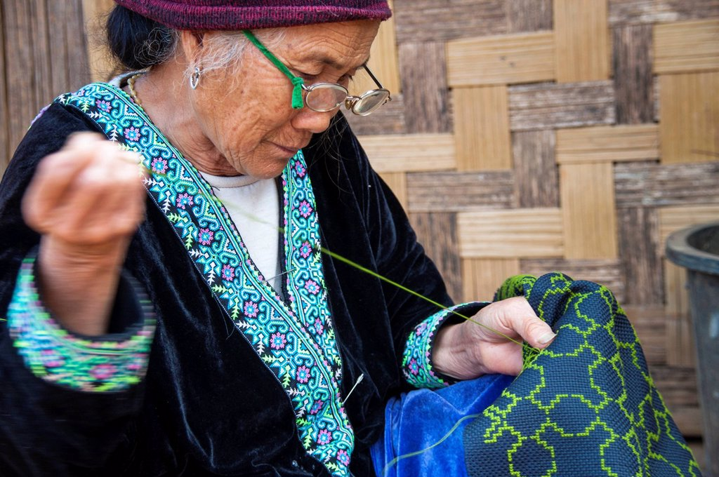 Stock Photo: 1848-651275 Elderly, traditionally dressed woman with glasses from the Black Hmong hill tribe, ethnic minority from East Asia, doing needlework, embroidery, Northern Thailand, Thailand, Asia