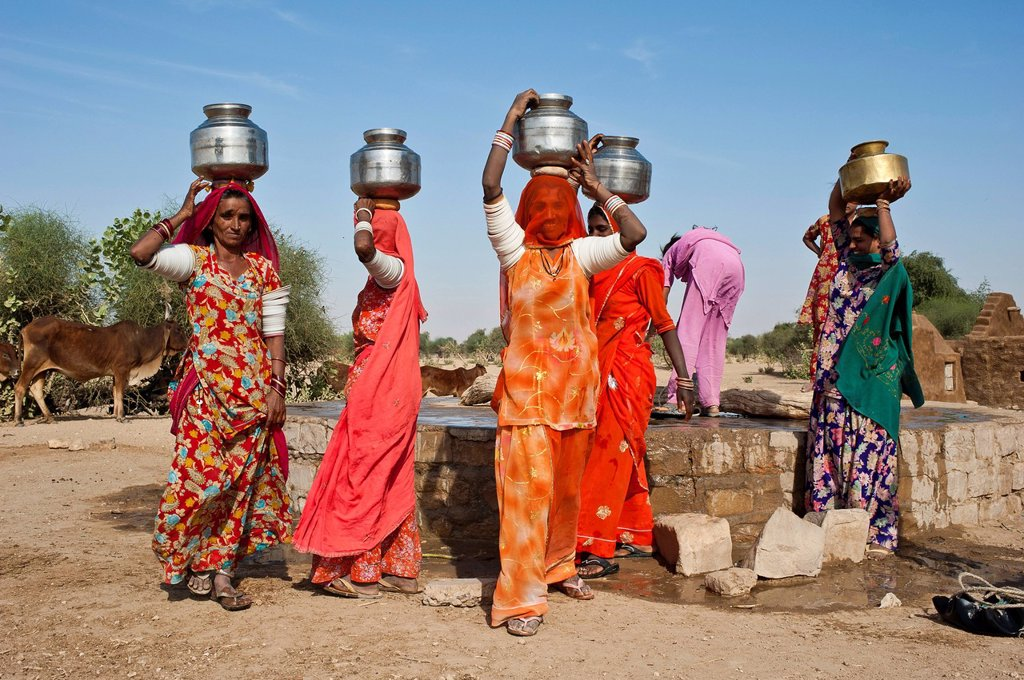 Indian women wearing saris carrying water jugs on their heads, they just filled the jugs at the well, Thar Desert, Rajasthan, India, Asia : Stock Photo