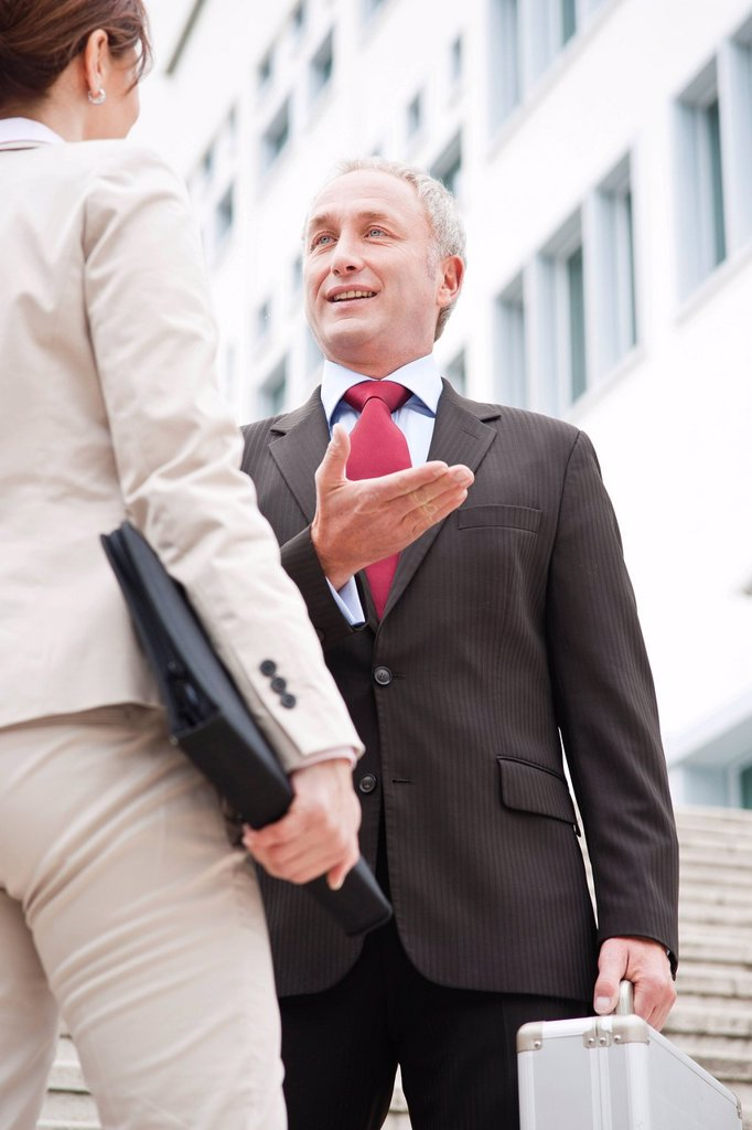 Stock Photo: 1848-652863 Businessman and businesswoman together in front of an office building