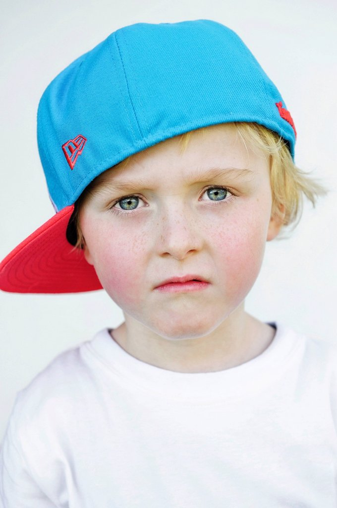 Stock Photo: 1848-652954 Little boy wearing a baseball cap with a sad face