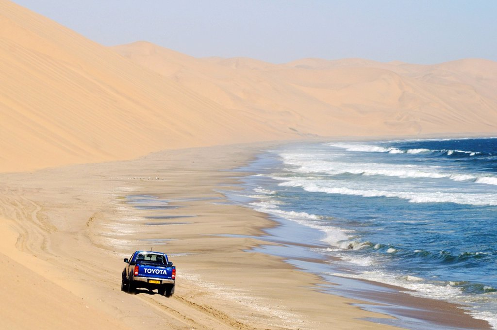 Off_road vehicle driving towards Sandwich Harbour on a beach on the Atlantic Ocean, Namib Naukluft National Park, part of the Namibian Skeleton Coast National Park, Skeleton Coast, Namib Desert, Namibia, Africa : Stock Photo