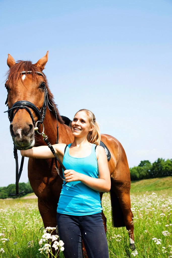 Stock Photo: 1848-653560 Girl patting her horse affectionately on the neck