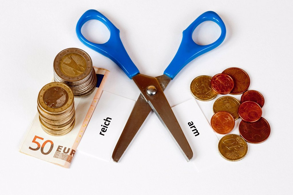 Open scissors with the signs reich and arm, German for rich and poor, with euro coins and banknotes, symbolic image for social inequality : Stock Photo