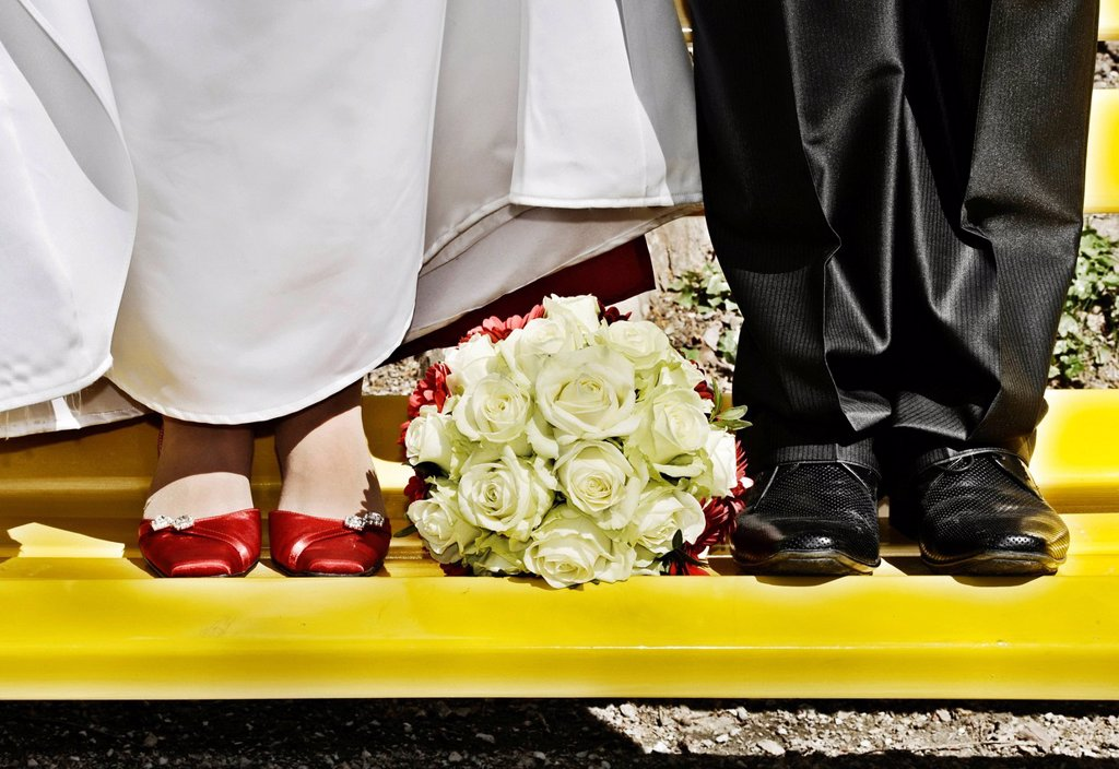 Bridal bouquet lying between the feet of the bride and the groom : Stock Photo