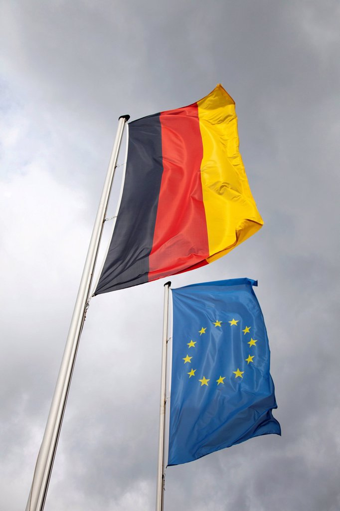 Stock Photo: 1848-654436 Dark clouds behind the flags of Germany and Europe