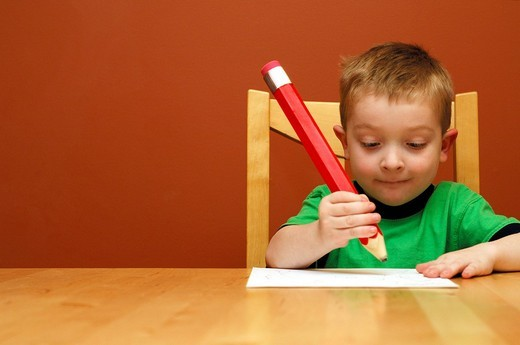 Boy writing with a big pencil : Stock Photo