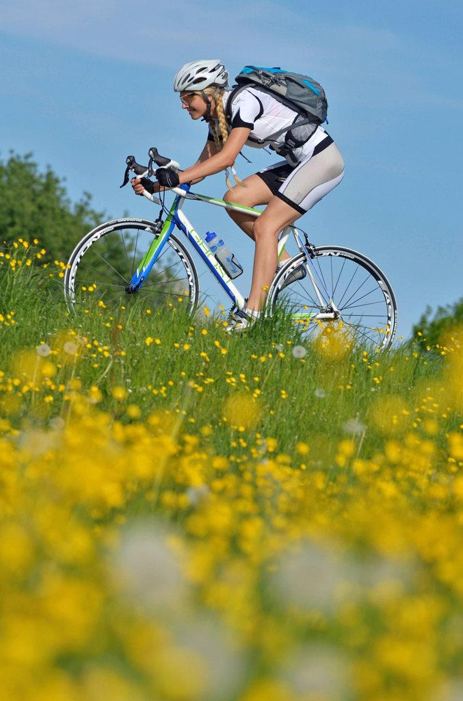 Young woman cycling on a road bike, Upper Bavaria, Bavaria, Germany, Europe : Stock Photo
