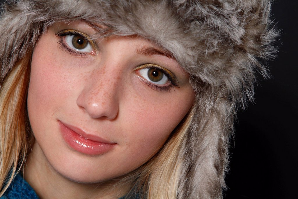 Young, blonde woman with a fur cap, 19 years, portrait : Stock Photo