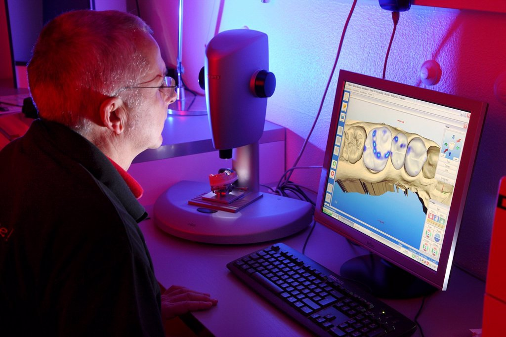 Dental laboratory, manufacture of a dental prostheses by a master craftsman, computer aided design for dental technology, constructing a dental bridge as a virtual model, the original cast is scanned, and after working on the computer, manufactured in a m. Dental laboratory, manufacture of a dental prostheses by a master craftsman, computer aided design for dental technology, constructing a dental bridge as a virtual model, the original cast is scanned, and after working on the computer, manufac : Stock Photo