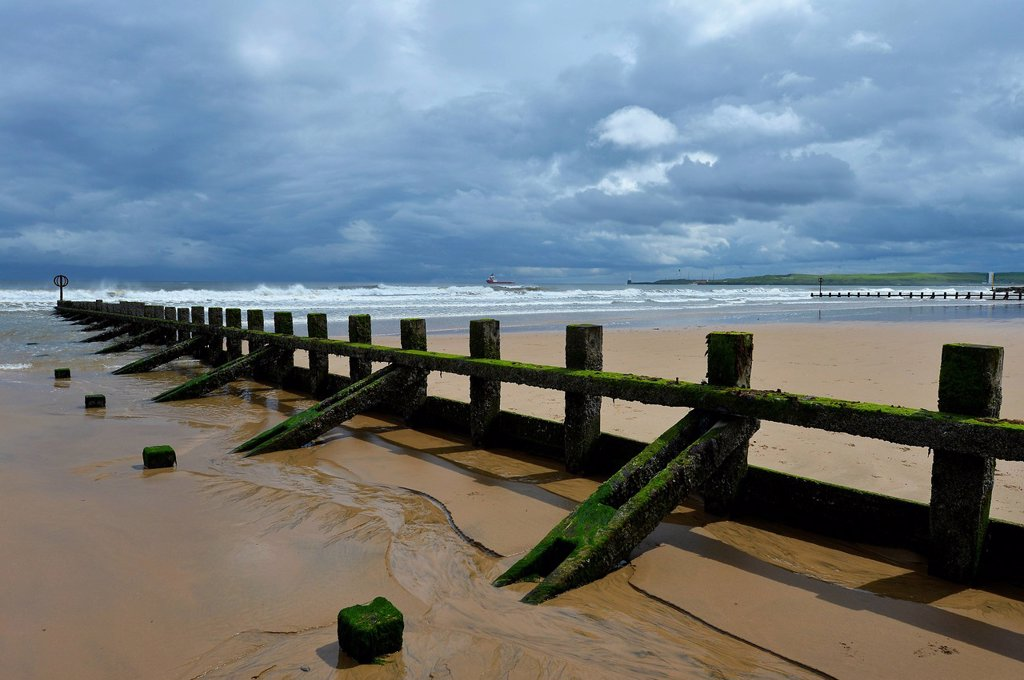 Thick, low hanging cloud cover above moss and algae covered groynes, breakwaters, at the beach, Aberdeen Scotland, United Kingdom, Europe : Stock Photo