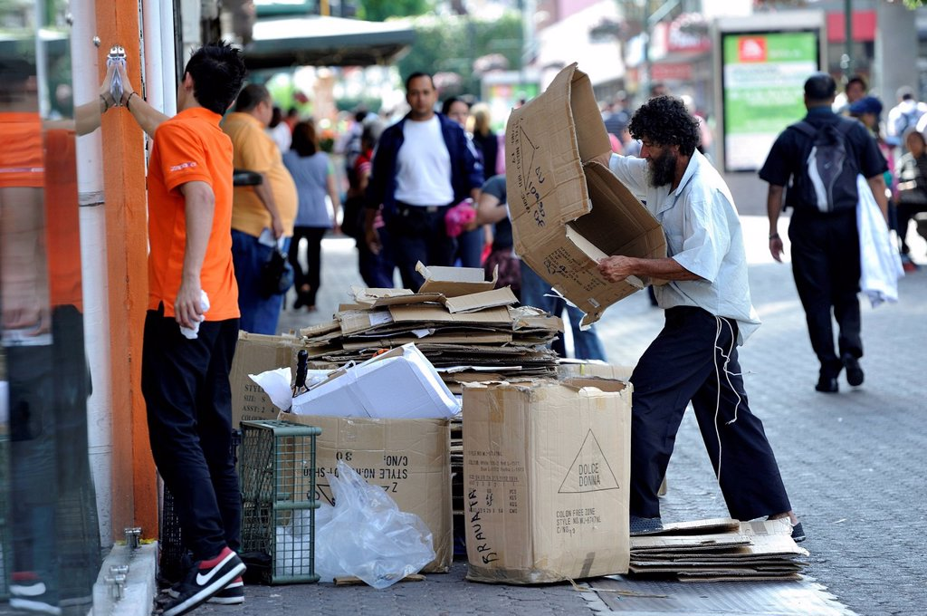 Stock Photo: 1848-658141 Poor man sorting recyclables or resources, cardboard boxes outside a shop, in order to sell them to a recycling plant, waste separation, pedestrian zone of San José, Costa Rica, Latin America, Central America