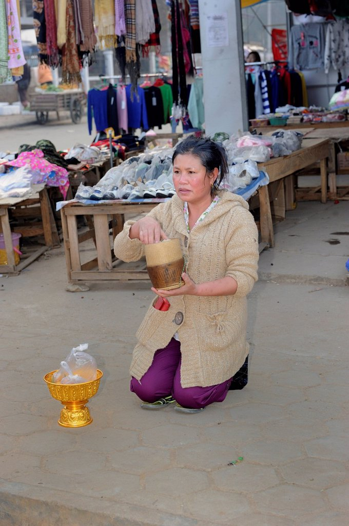 Buddhist shopkeeper waiting with offerings for the Buddhist mendicants in the early morning in the town of Phonsavan, Laos, Southeast Asia, Asia : Stock Photo