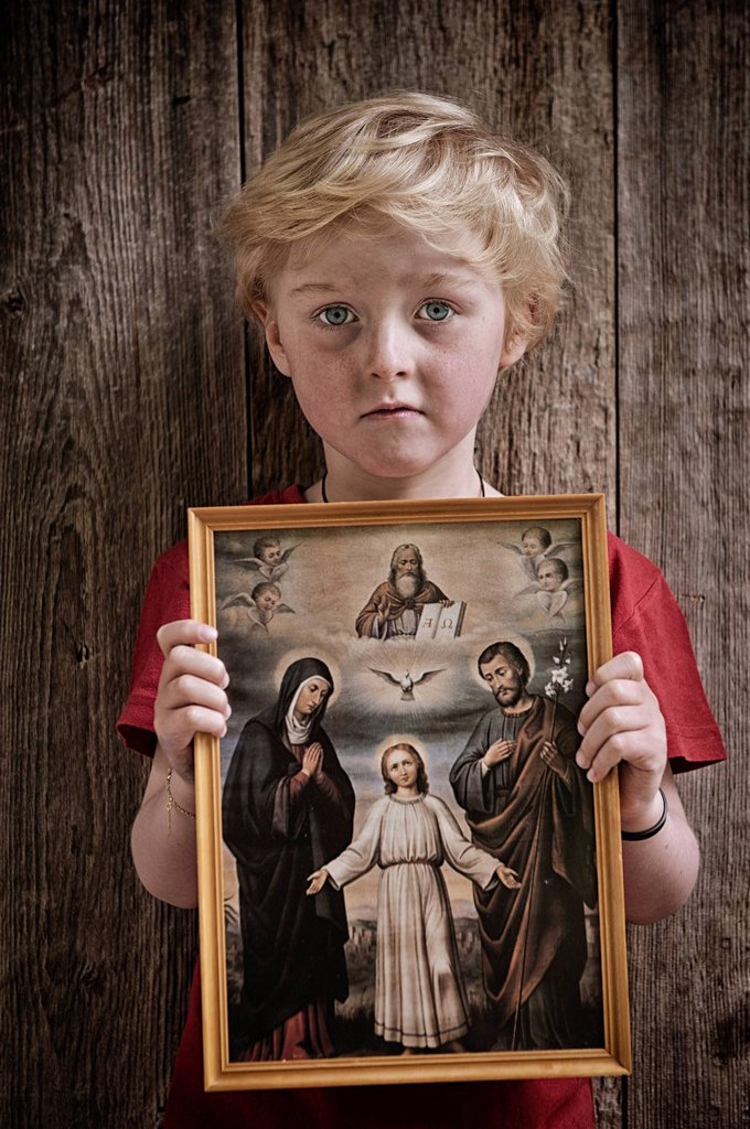 Boy holding a Christian image of saints, with Jesus, Mary and Joseph, pneuma : Stock Photo
