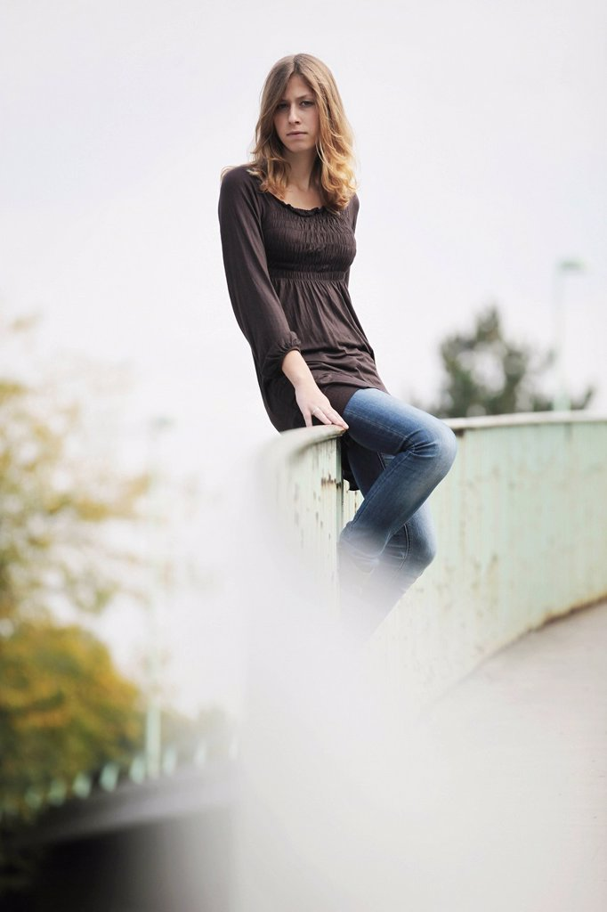 Stock Photo: 1848-660345 Young woman sitting on a railing, in an urban environment
