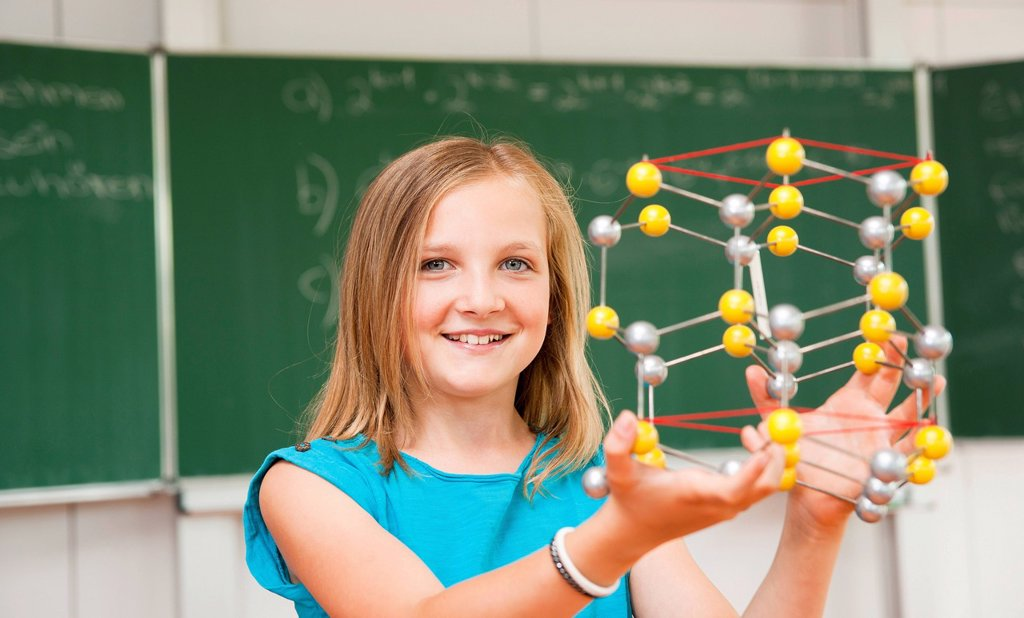 Stock Photo: 1848-660459 Schoolgirl in a classroom with a model of an atom