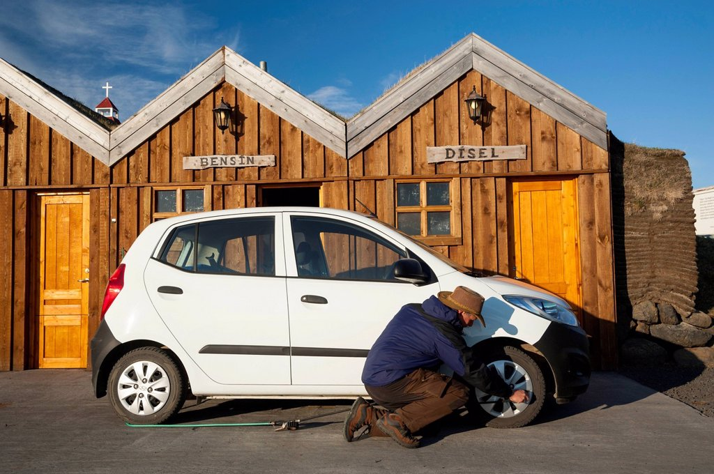 Stock Photo: 1848-661084 Man kneeling next to a car checking the tyre pressure, petrol station in a wooden hut, Moeðrudalur, Highlands of Iceland, Iceland, Europe