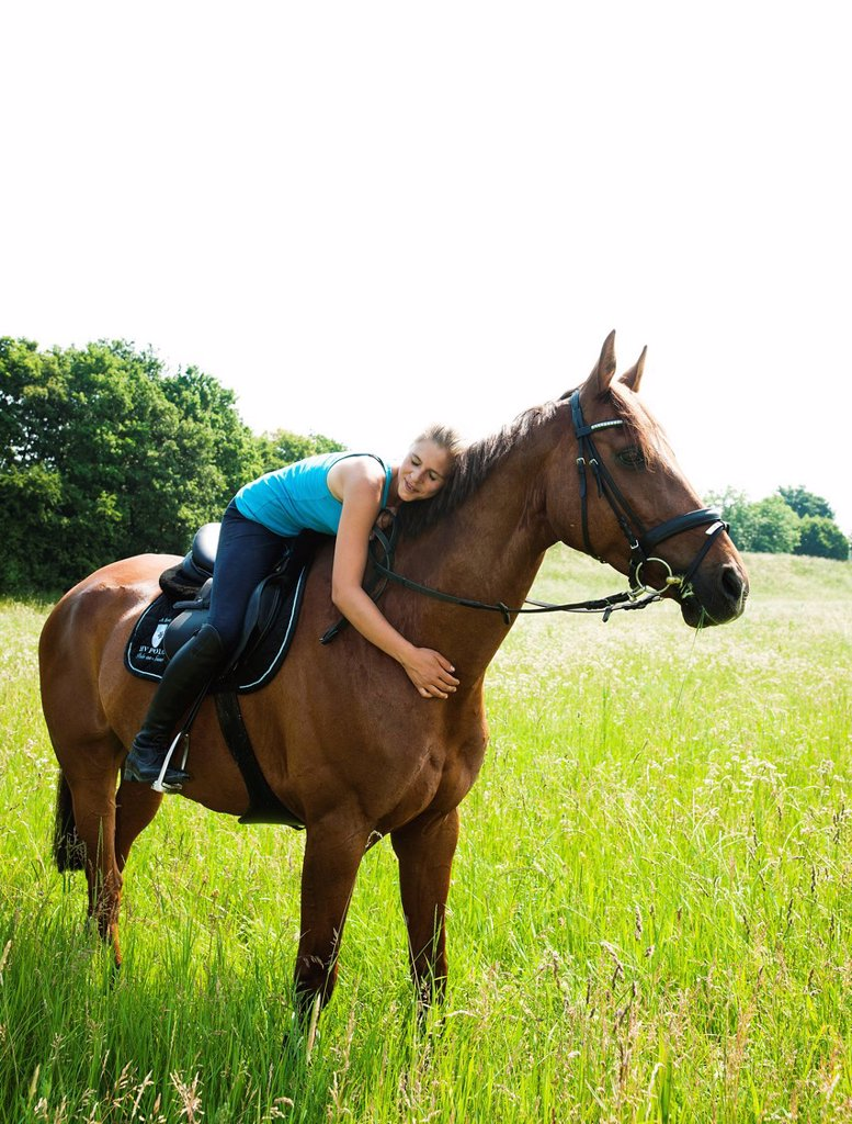 Stock Photo: 1848-661332 Smiling girl lying down on the neck of her horse