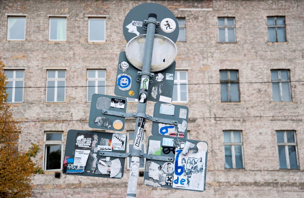 Stock Photo: 1848-661485 Road signs seen from behind with stickers in front of the facade of a building on Oranienburgerstrasse, Berlin, Germany, Europe