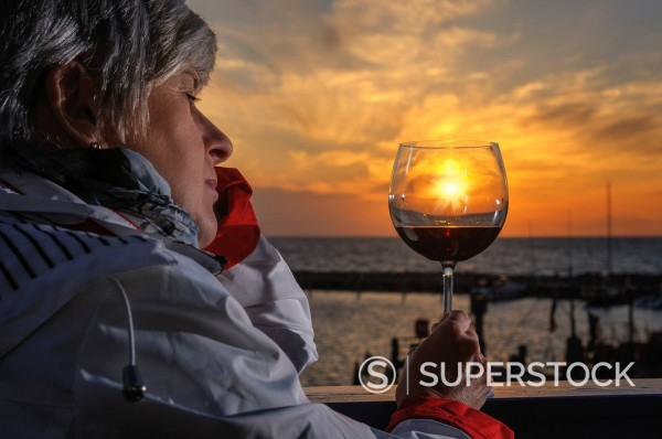 Woman sitting with a glass of red wine on the balcony by the sea at sunset, Timmendorf, Mecklenburg_Western Pomerania, Germany, Europe : Stock Photo