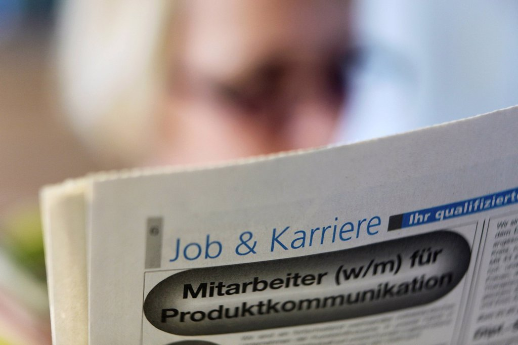 Stock Photo: 1848-665725 Woman looking for a job, reading the newspaper
