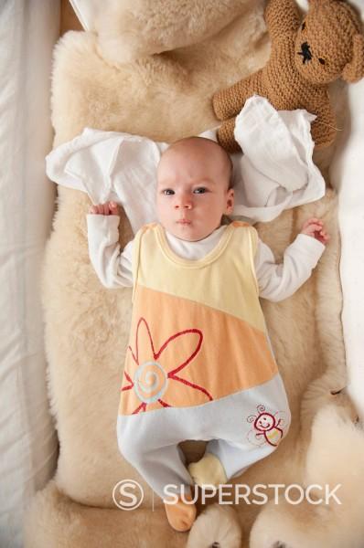 Baby girl, 7 weeks, lying on a fleece wearing a romper suit, kicking : Stock Photo