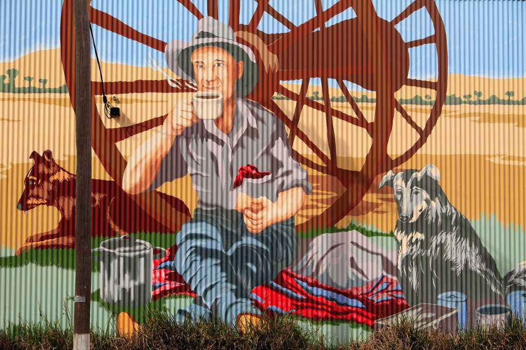 Hand_painted wall mural on corrugated iron of an Australian farmer drinking a hot beverage with his two dogs, Carnamah, Western Australia, Australia : Stock Photo