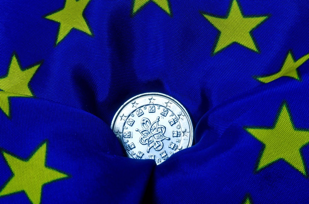 Stock Photo: 1848-668718 Portuguese euro coin lying on an European flag, going down, symbolic image