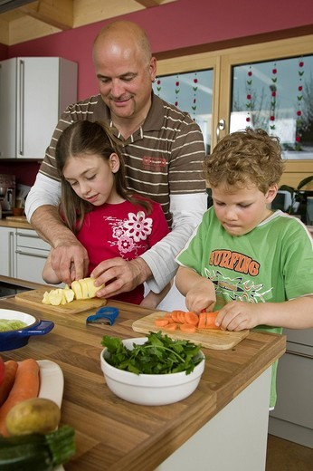 Father, children, cooking together : Stock Photo