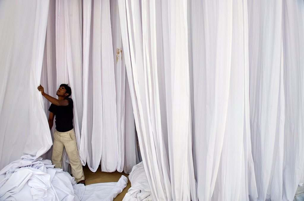 Man in front of white_coloured fabric, Sanganer dyeing centre near Jaipur, Rajasthan, India, Asia : Stock Photo