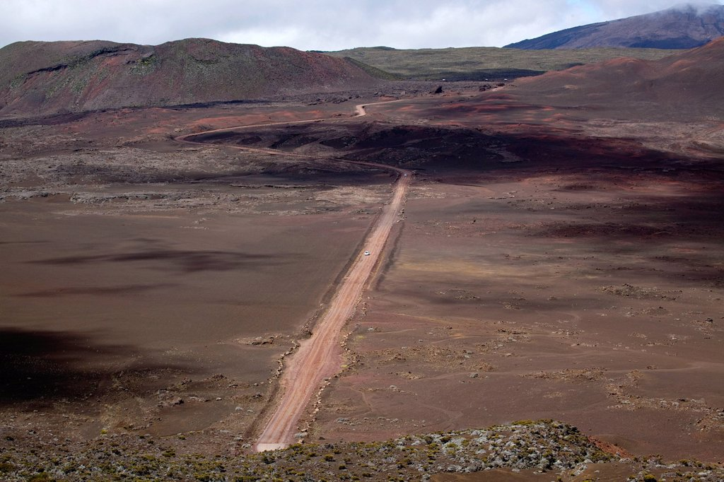 Dirt road on the Plaine des Sables plateau at the foot of the Piton de la Fournaise volcano, La Reunion island, Indian Ocean : Stock Photo