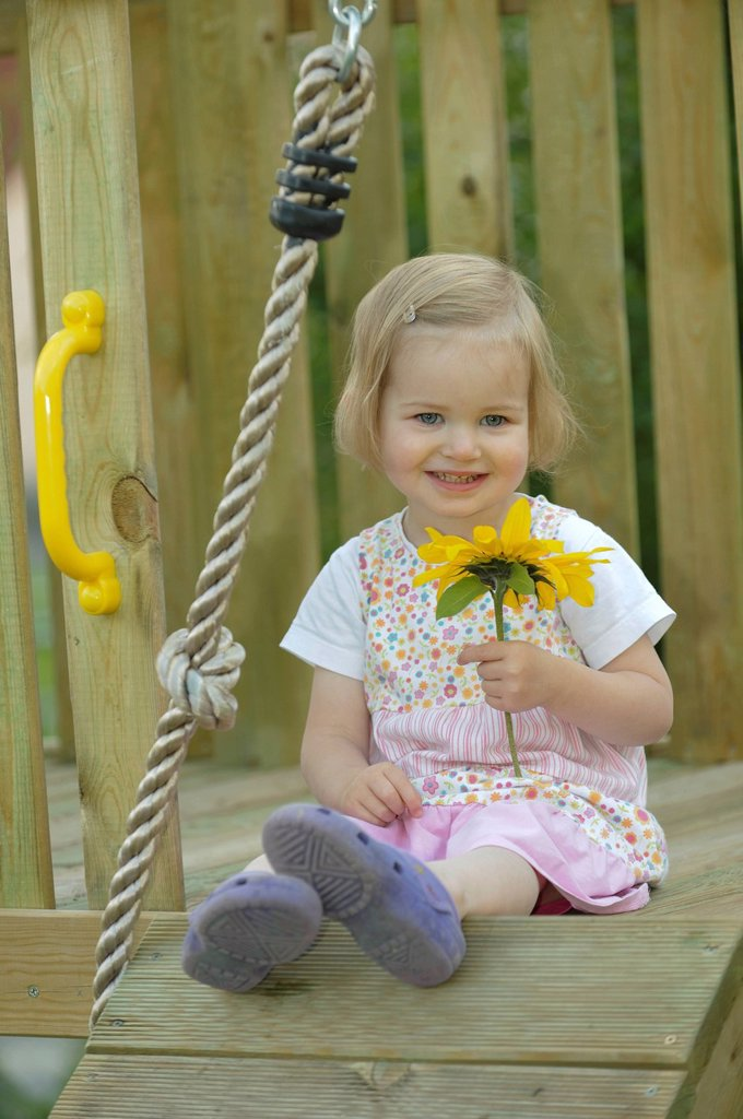 Stock Photo: 1848-672364 Smiling 2_year_old girl with a sunflower in a play house