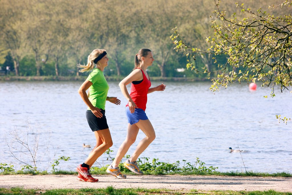 Stock Photo: 1848-673464 Two recreational runners, young women, 25_30 years, jogging on a lakeside path