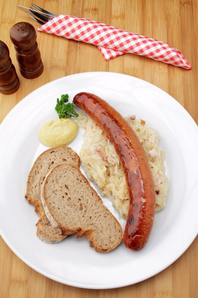 Stock Photo: 1848-673588 Krakowska smoked spicy Polish sausage on sauerkraut, crusty bread and mustard