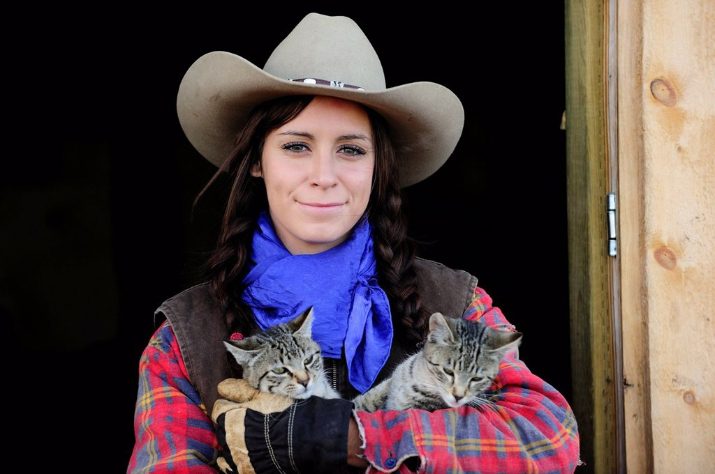 Stock Photo: 1848-677243 Cowgirl with two cats, portrait, Saskatchewan, Canada, North America