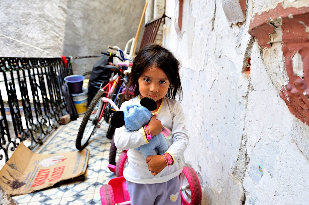 Indigenous girl with a stuffed animal, living with her community in a dilapidated house from the colonial period in the centre of Mexico City, Ciudad de Mexico, Mexico, Central America : Stock Photo