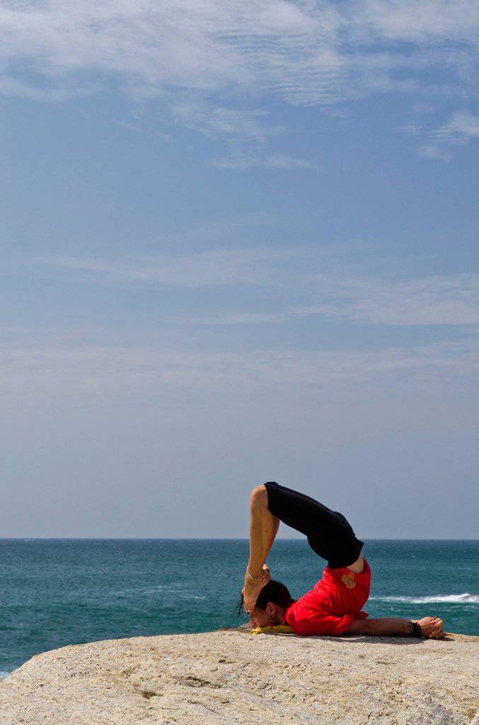Stock Photo: 1848-679613 Woman in a yoga position, Salabhasana, by the sea in Kanyakumari, Tamil Nadu, India, Asia