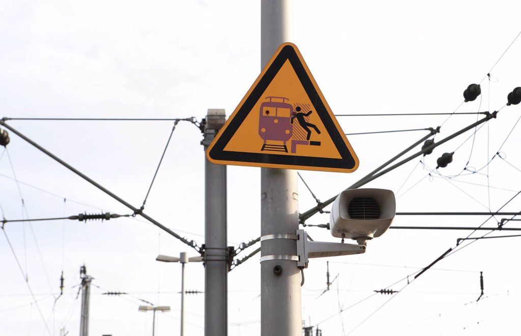 Speaker, overhead lines and a warning sign on a railway station : Stock Photo